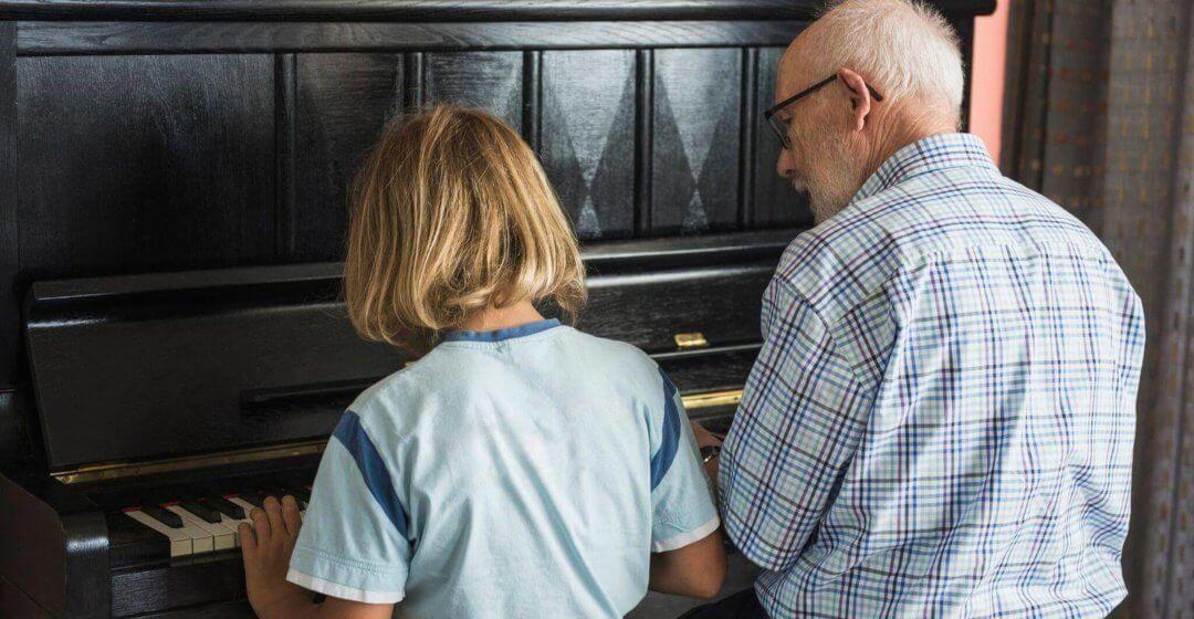 Opa und Enkel spielen am Klavier